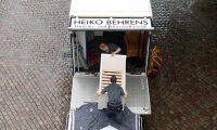 Zwei Mitarbeiter von Behrens tragem ein Regal in ein LKW