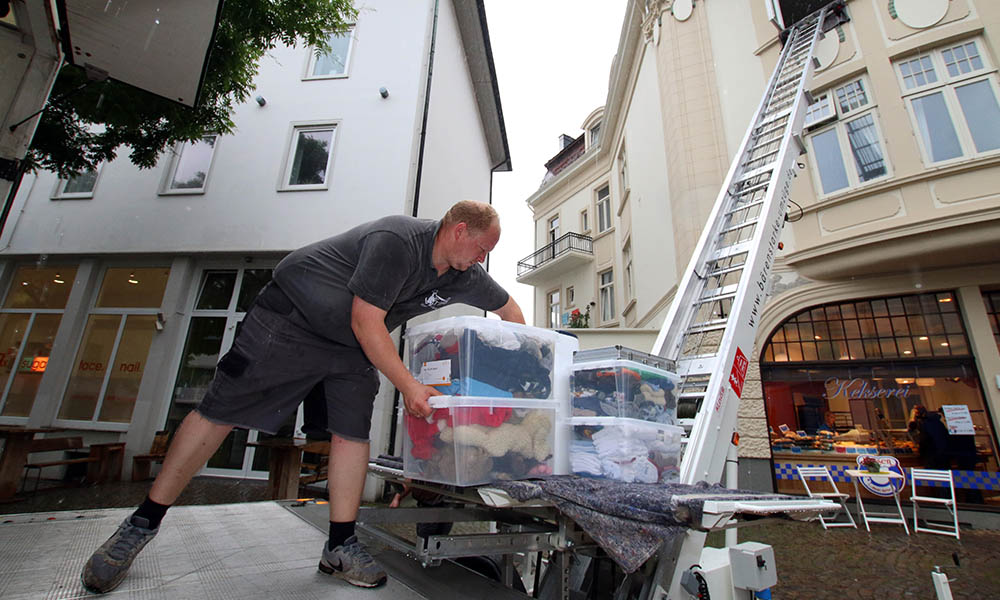 Ein Mitarbeiter von Heiko Behrens trägt Gegenstände in einen LKW