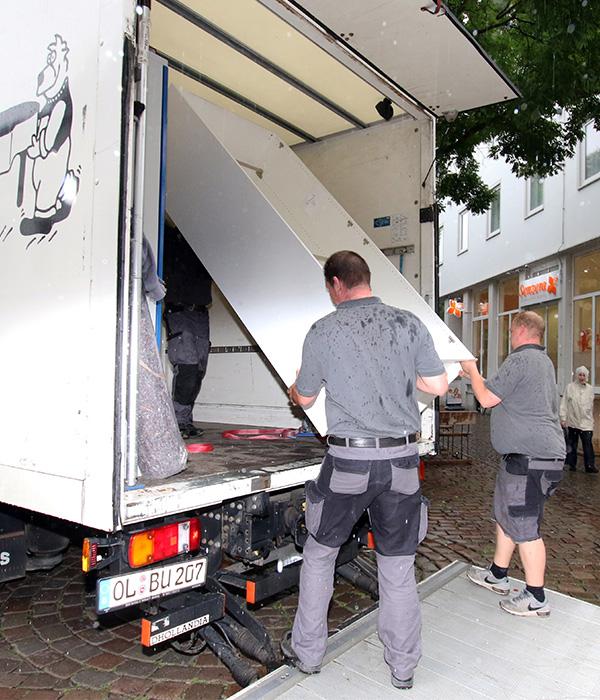 Zwei Mitarbeiter von Heiko Behrens tragen Möbel in einen LKW