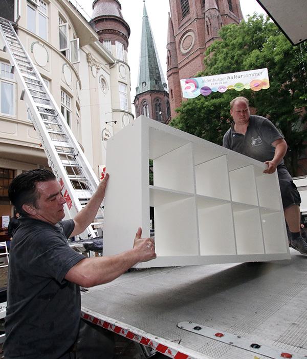 Zwei Behrens Mitarbeiter tragen ein Regal in einen Transporter