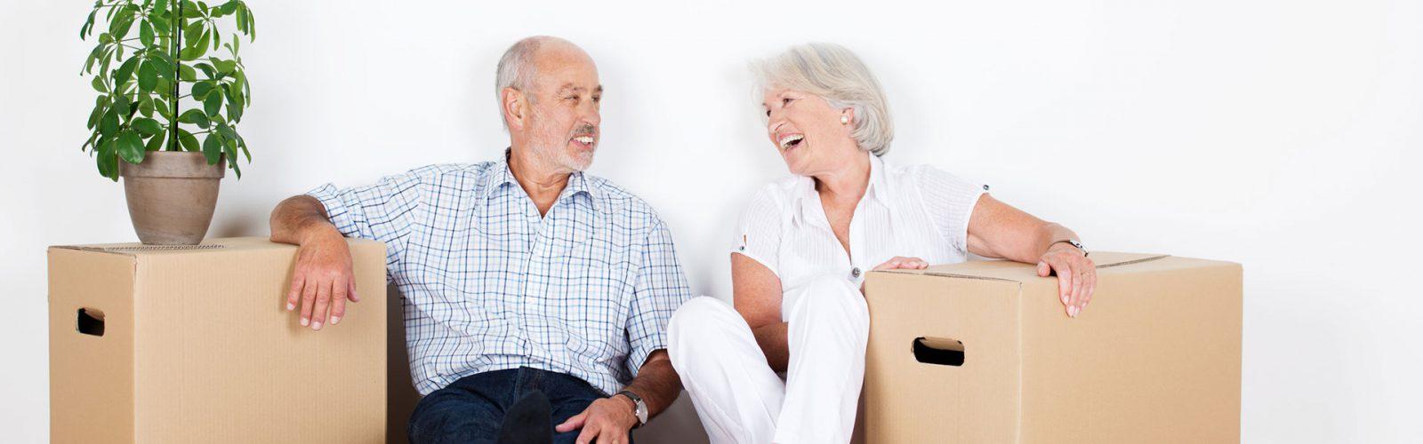 Seniorenpärchen Sitzt auf dem Boden neben zwei Umzugskartons